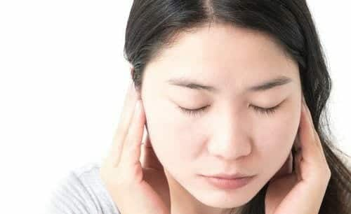 Closeup woman suffering from tinnitus with hands over ears