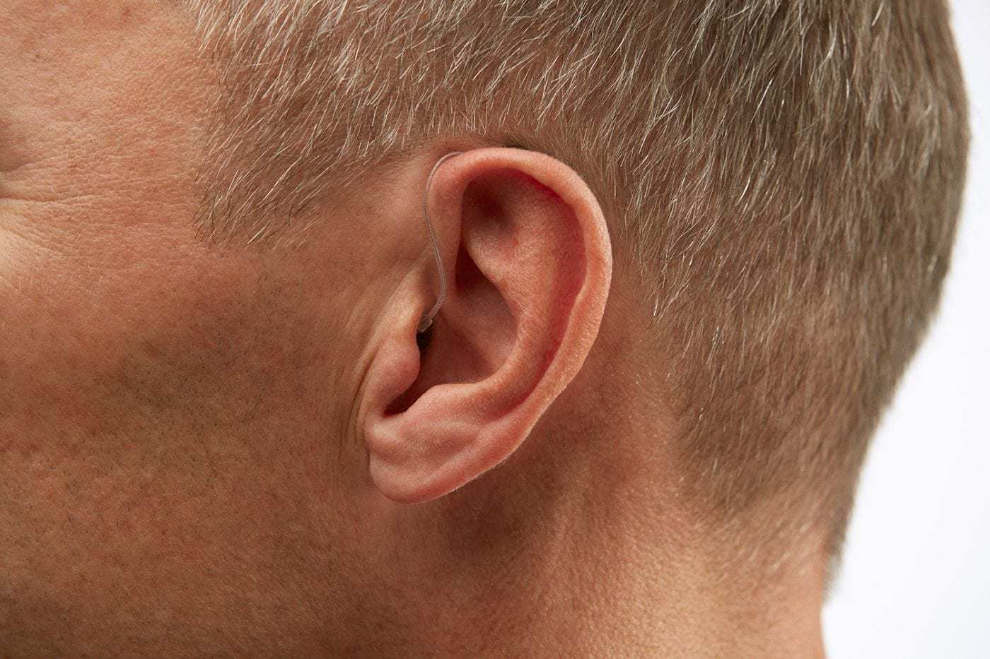 close-up of ear with barely visible hearing aid