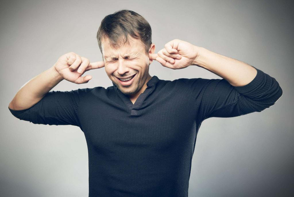 man sticking his fingers in his ears