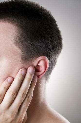 Man touching his ear as it bothers him