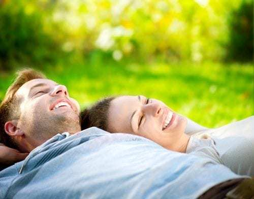 Young Couple Lying on Grass and Smiling