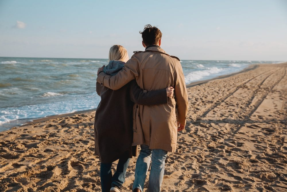 couple with arms around each other walking on beach