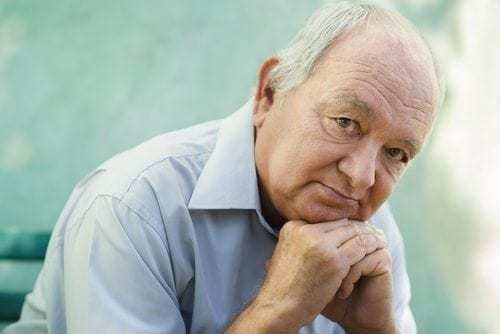 older man looking at camera with thoughtful expression