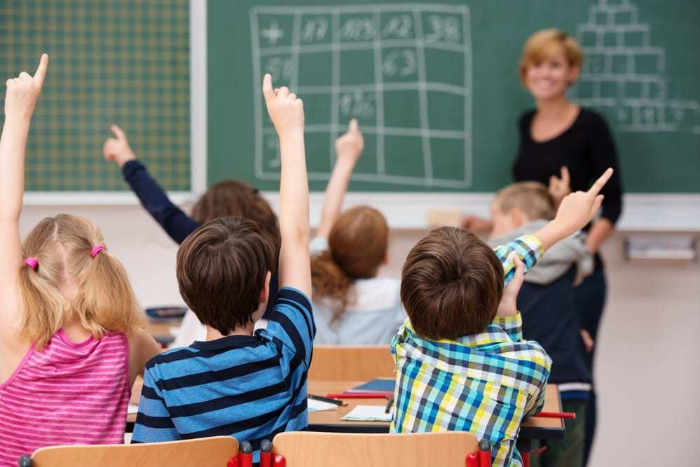young school children all raising their hands to answer a question
