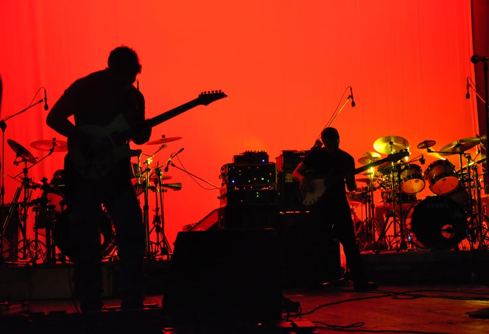 silhouette of rock band on stage, red lighting