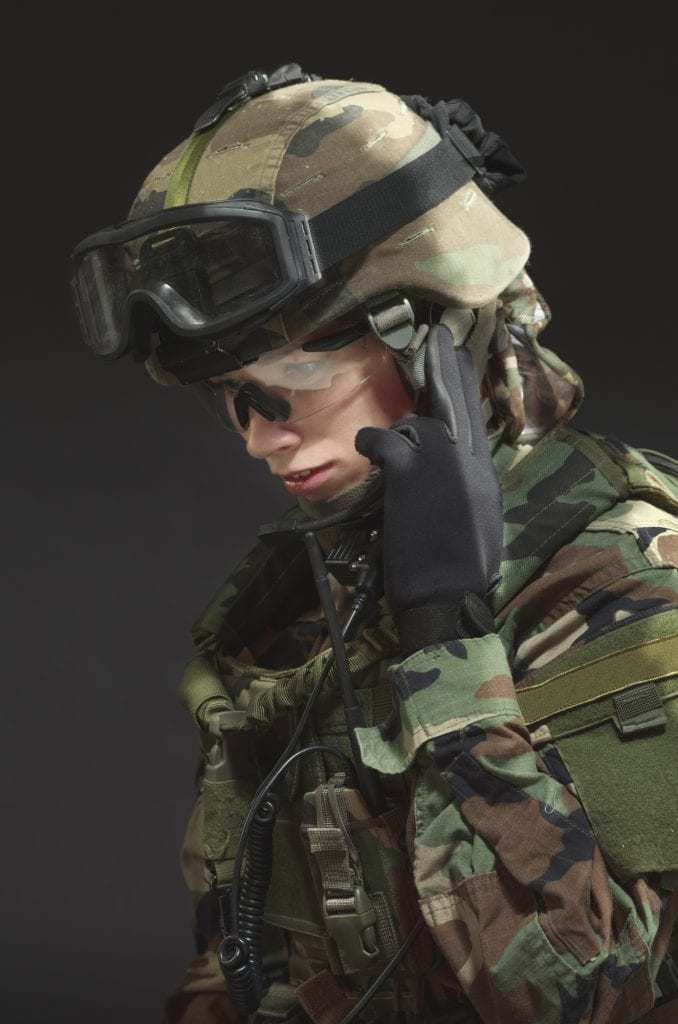 female soldier in full gear holding fingers to ear