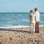 Older Couple Standing on Beach, Looking at Waves, His Arm Around Her