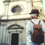 Woman with backpack in front of old building